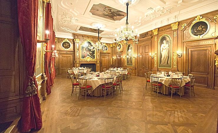 Gouden Zaal **Gouden Zaal van Mauritshuis is een onvergetelijke evenementenlocatie. Deze ruimte is dankzij haar prachtig decor de perfecte keuze voor uw evenement en zal een blijvende indruk nalaten op al uw gasten.**  Het Mauritshuis biedt verschillende kamers, elk met een eigen sfeer, variërend van monumentaal tot modern.  Het 17e-eeuws gebouw herbergt de prachtige Gouden Zaal met fonkelende kroonluchters en plafondschilderingen van Pellegrini. Een koninklijke locatie voor het ontvangen van gasten omringd door kunst uit de Gouden Eeuw. De Gouden Zaal biedt plaats aan 70 gasten tijdens een diner en ruimte voor 100 bij recepties. Bovendien is de kamer ook geschikt voor presentaties en vergaderingen van maximaal 80 personen.