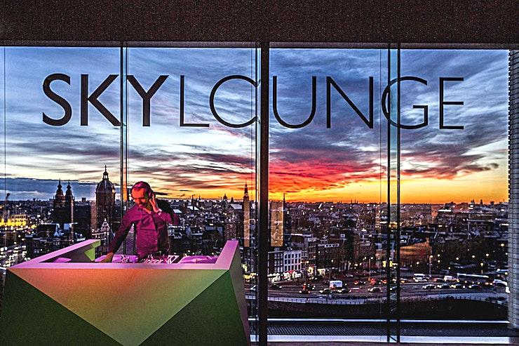 Main Bar **The SkyLounge Amsterdam Main Bar is één van de mooiste ruimtes in heel Amsterdam en is beschikbaar voor verhuur voor levendige en stijlvolle recepties.**  Elke metropool heeft een unieke plek om de stad vanaf grote hoogte te ontdekken. Amsterdam heeft de SkyLounge Amsterdam, een bekroonde dak lounge bar met uitzicht op deze unieke metropool. Dit is de plaats waar de inwoners van Amsterdam en wereldreizigers elkaar ontmoeten. SkyLounge Amsterdam biedt u een panoramisch uitzicht op de meest energieke hoofdstad van Europa, 365 dagen per jaar. Reserveringen kunnen gemaakt worden voor groepen boven de 20 personen.