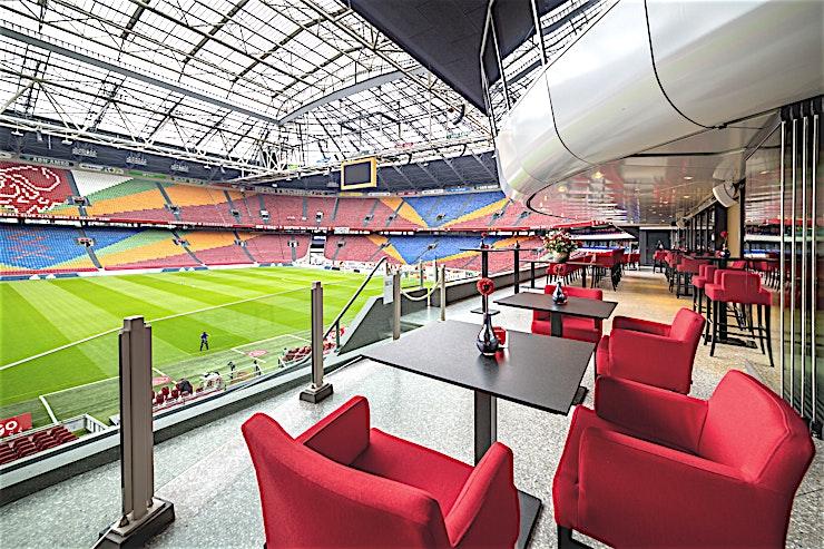 Royal Box **The Royal Box heeft een geweldig zicht op het Johan Cruijff Stadion. Deze ruimte is ontworpen voor uw volgende receptie in Amsterdam.**  Een adembenemend uitzicht op het stadion, culinaire hoogstandjes en een chique bar. De Royal Box is de ultieme plek om uw gasten te verwelkomen.  Nergens beter dan hier kunt u de grandeur en de dynamiek van het stadion ervaren. De Royal Box biedt een prachtig uitzicht op het stadion en kan uitstekend worden gecombineerd met de Skybar.  In het hart van het stadion vindt u de Boardroom, een unieke locatie met uitzicht op het veld. Deze kamer heeft een zeer gezellige sfeer en is een spectaculaire locatie voor een exclusieve bijeenkomst, lunch, diner of een drankje.  Geef uw gasten een echte VIP-behandeling. In de Royal Box kunt u uw gasten trakteren op een heerlijk diner of een exclusieve lunch.  Laat uw gasten de roem van de Johan Cruijff ArenA ervaren tijdens uw evenement. Combineer de capaciteit van de zalen met het immense stadion als achtergrond. Dit zal uw verhaal specialer te maken! Gebruik het veld of de hoofdtribune als omgeving voor uw evenement.