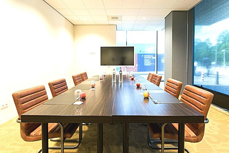 1e Kamer **1e Kamer is een stijlvolle vergaderlocatie van Babylon Hotel Den Haag.**   Babylon complex, gelegen direct naast het Centraal Station van Den Haag,  is gemakkelijk bereikbaar met de auto en natuurlijk ook met het openbaar vervoer. Het heeft 7 verschillende zalen die gecombineerd kunnen worden in een multifunctionele wijze. Alle kamers zijn uitgerust met state-of-the-art audiovisuele apparatuur en hun eigen Wi-Fi-netwerk. De kamers variëren van 35 m² tot 200 m² en via onze partner, New Babylon Meeting Center, kunnen we zelfs ruimtes tot 600 m² aanbieden!   Alle bekende attracties liggen binnen handbereik, maar je zult ook meer dan een handvol van de speciale boetieks en hotspots in de directe omgeving vinden. Veel van de Nederlandse ministeries en overheidsinstanties zijn op loopafstand. Met de tram aan de ingang van het hotel bevindt u zich in no-time op de boulevard van Scheveningen.