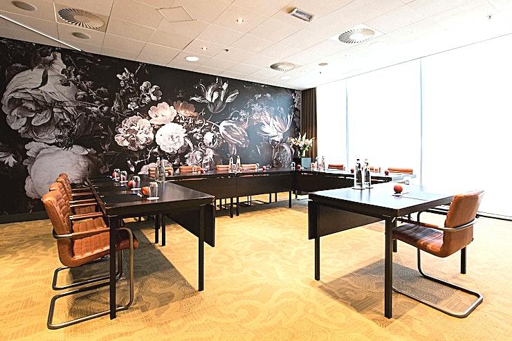 Noordeinde **Op zoek naar een elegante en trendy vergaderruimte te huren in de stad? Zoek niet verder, Noordeinde in Babylon Hotel Den Haag is een opmerkelijke vergaderlocatie!**   Babylon complex, gelegen direct naast het Centraal Station van Den Haag,  is gemakkelijk bereikbaar met de auto en natuurlijk ook met het openbaar vervoer. Het heeft 7 verschillende zalen die gecombineerd kunnen worden in een multifunctionele wijze. Alle kamers zijn uitgerust met state-of-the-art audiovisuele apparatuur en hun eigen Wi-Fi-netwerk. De kamers variëren van 35 m² tot 200 m² en via onze partner, New Babylon Meeting Center, kunnen we zelfs ruimtes tot 600 m² aanbieden!   Alle bekende attracties liggen binnen handbereik, maar je zult ook meer dan een handvol van de speciale boetieks en hotspots in de directe omgeving vinden. Veel van de Nederlandse ministeries en overheidsinstanties zijn op loopafstand. Met de tram aan de ingang van het hotel bevindt u zich in no-time op de boulevard van Scheveningen.